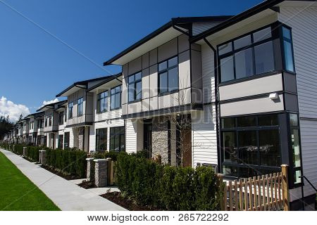Residential Townhouses On Blue Sky Background On Sunny Day. External Facade Of A Row Of Colorful Mod