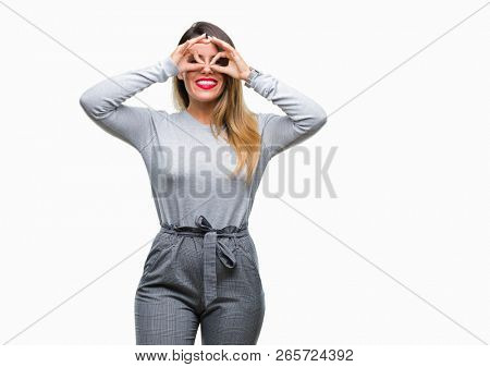 Young beautiful worker business woman over isolated background doing ok gesture like binoculars sticking tongue out, eyes looking through fingers. Crazy expression.
