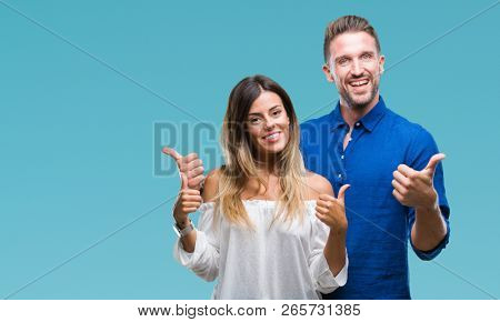 Young couple in love over isolated background success sign doing positive gesture with hand, thumbs up smiling and happy. Looking at the camera with cheerful expression, winner gesture.