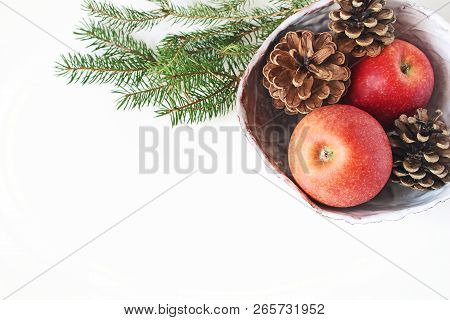 Closeup Of Red Apple Fruit And Pine Cones In Ceramic Bowl And Spruce Tree Branches On White Table Ba
