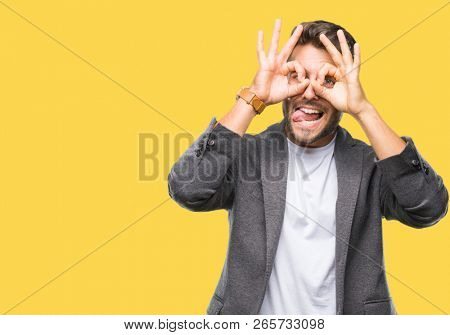 Young handsome business man over isolated background doing ok gesture like binoculars sticking tongue out, eyes looking through fingers. Crazy expression.