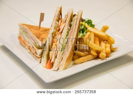 A Chicken Club Sandwich With French Fries