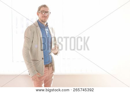 Smiling Businessman With Eyeglasses With Touchpad Sitting At Workplace In Office