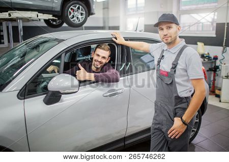 Happy Owner Sits In Car And Smiles. He Holds His Big Thumb Up. Worker Stand At Car And Holds His Han