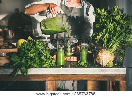 Woman Pouring Green Smoothie From Blender To Bottle