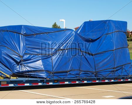 Oversize Load With Tarps Over Lowboy Cargo. The Usual Loads Are New Or Used Manufacturing Machinery