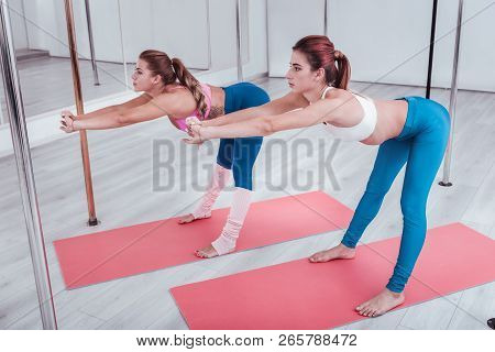 Two Pole Dancers Stretching Their Legs And Backs In Pole Dance Studio