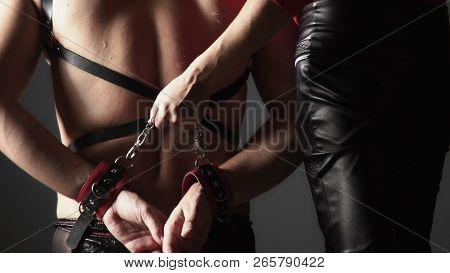 Couple, Unrecognizable Men And Women. A Woman Dominates A Man With A Whip. Mens Back In A Harness.