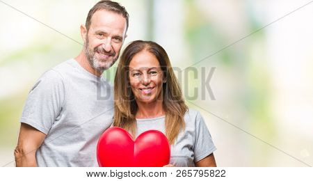 Middle age hispanic casual couple in love holding red heart over isolated background with a happy face standing and smiling with a confident smile showing teeth