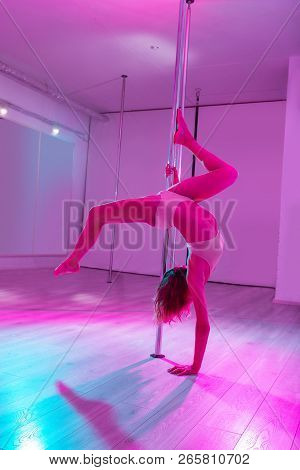 Pole Dancer Holding The Pole While Practicing New Moves In Studio