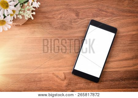 Black Portable Phone On Wooden Isolated Table. Top View. Horizontal Composition.