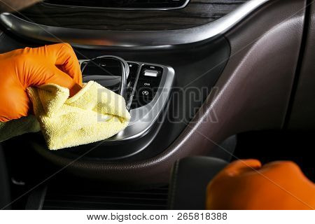 A man cleaning car with microfiber cloth. Car detailing. Selective focus. Car detailing. Cleaning with sponge. Worker cleaning. Microfiber and cleaning solution to clean. poster