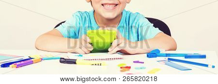 Boy With Calculator Doing Homework At Home. Child Is Sitting At A Desk Indoors. Back To School. Peop
