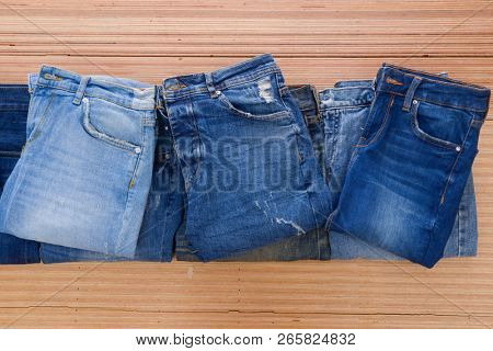 pile of Blue jeans on a brown wooden background