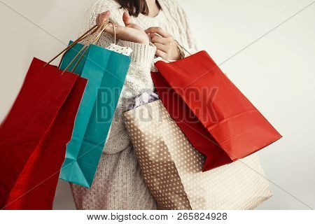 Christmas Shopping And Seasonal Sale. Happy Girl In Sweater Holding Red And Green Paper Shopping Bag