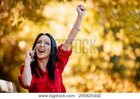 Excited Happy Young Woman Listening Very Good News On Smartphone And Get Very Happy In Autumn Nature