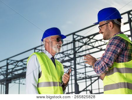 Senior Engineer And Construction Worker Talking In Front Of Metal Structure At Building Site