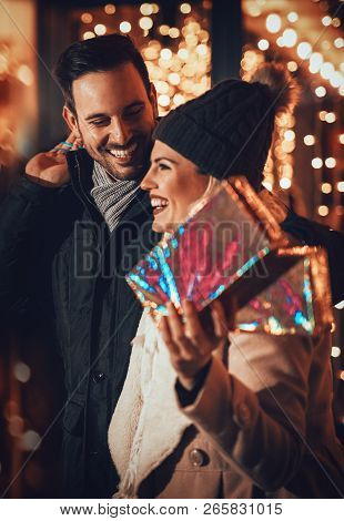 Young Happy Smiling Couple In Shopping Passes In Front Of Shopping Mall. Girl Is Carrying Gift Boxes
