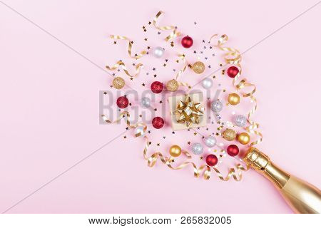 Champagne Bottle With Confetti Stars, Gift Box And Holiday Balls On Pastel Pink Background. Christma