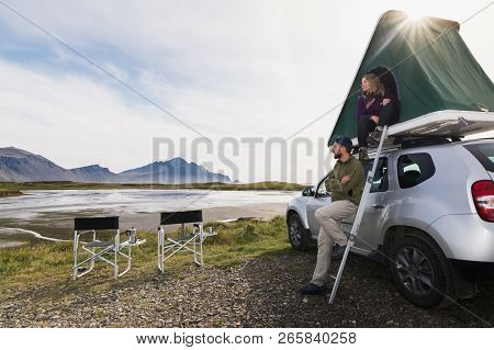 Hofn, Iceland - August 2018: Young Couple Sitting On A Ladder Next To Offroad Car With Tent On The R