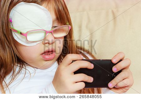 Childhood, childcare, being polite concept. Little toddler girl with bandage on eye playing games on smartphone poster