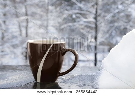 Steamy Cup With A Hot Drink On The Edge Of A Balcony, With Ice And Snow, Snowy Trees In The Backgrou