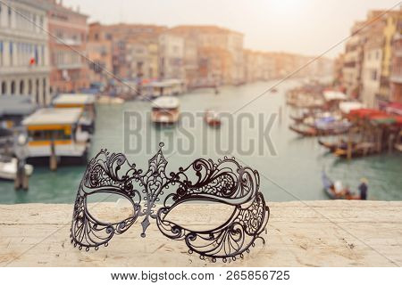 Venetian Masks On Bridge Agaist Landscape Grand Canal With Gondolas And Boats In Venice, Italy . Ann