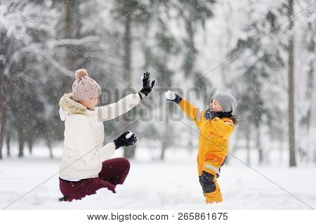 Cute Little Boy And Grandma / Babysitter / Mother Playing Snowballs In Winter Park. Family Winter Fu