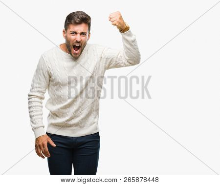 Young handsome man wearing winter sweater over isolated background angry and mad raising fist frustrated and furious while shouting with anger. Rage and aggressive concept.