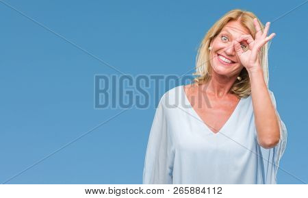 Middle age blonde business woman over isolated background doing ok gesture with hand smiling, eye looking through fingers with happy face.