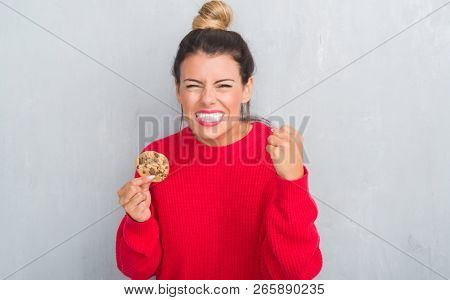 Young adult woman over grey grunge wall eating chocolate chip cooky annoyed and frustrated shouting with anger, crazy and yelling with raised hand, anger concept