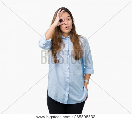 Young beautiful brunette business woman over isolated background doing ok gesture shocked with surprised face, eye looking through fingers. Unbelieving expression.