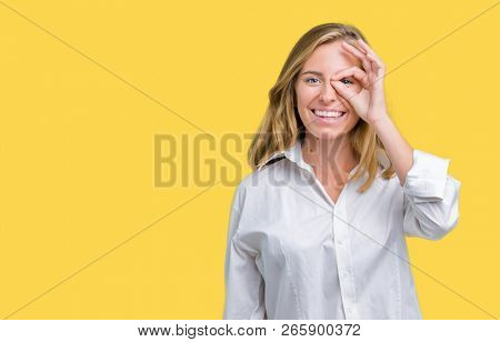 Beautiful young business woman over isolated background doing ok gesture with hand smiling, eye looking through fingers with happy face.