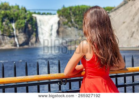Quebec city sightseeing tourist woman at Chute montmorency falls quebec popular attraction. Young lady in red summer dress looking at waterfalls outdoor.
