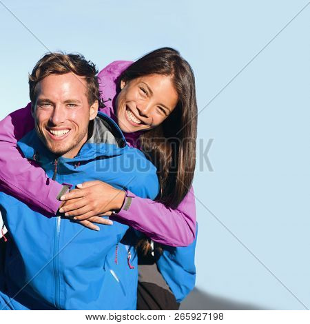 Happy hikers couple living an active lifestyle hugging laughing outdoors on trek hike nature. Healthy young people adventure fun wearing jackets. Interracial relationship, Asian woman, Caucasian man
