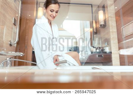 Woman in luxurious hotel bathroom letting water in the bathtub in animation of a relaxing experience