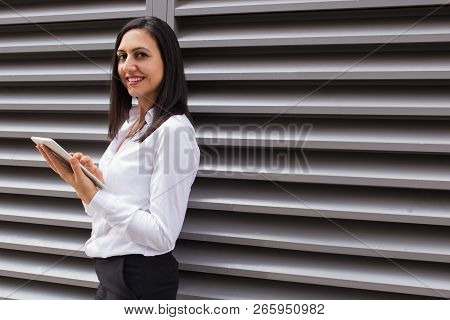 Portrait Of Happy Young Businesswoman Using Digital Tablet Outdoors. Caucasian Female Student Standi
