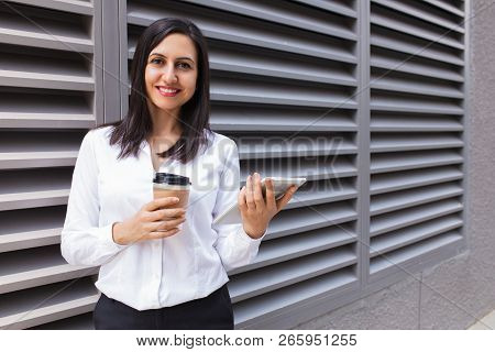 Portrait Of Smiling Young Businesswoman With Coffee And Touchpad. Caucasian Woman Using Digital Tabl