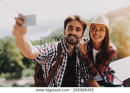 Couple Sitting On Concrete Ledge Taking Selfie. Young Man And Attractive Woman With Backpacks Sittin
