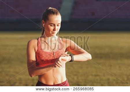 Athletic Attractive Blonde Long Haired Woman In Sportswear Standing At The Football Stadium And Chec