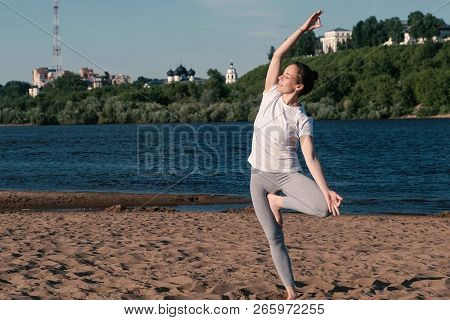 Woman Stretching Yoga On The Beach By The River In The City. Beautiful City View. Vrikshasana Pose.