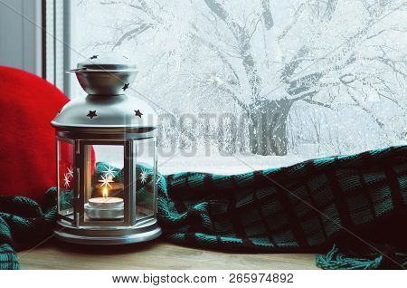 Winter background-lantern with candle and plaid with pillow on windowsill and winter scene outdoors. Still life with winter concept Winter evening with cold winter weather outdoors. Winter composition
