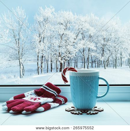 Winter Christmas background. Cup with Christmas candy cane on windowsill and winter trees outdoors. Winter festive composition with Christmas mood, winter Christmas still life