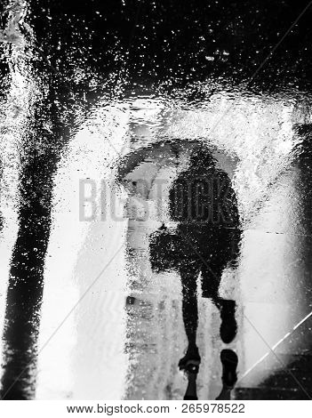 Abstract image of rain in New York City. Reflections from wet tile slabs. Pedestrians hurry on their business. Motion blur image poster