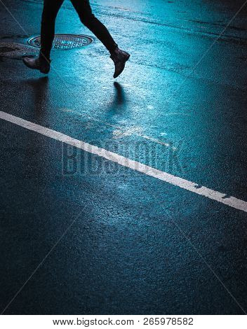 Lights And Shadows Of New York City. Silhouette Of A Man Running Down The Street. Reflection Of Neon