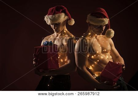 New Year Strip And Gifts For Adults. Twins Santa With Muscular Body In Garland. Christmas Party And