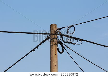 Concrete Utility Pole With Multiple Black Electrical Wires Connected And Going In Various Directions