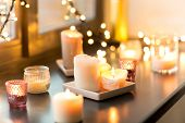 hygge, decoration and christmas concept - candles burning in lanterns and festive garland on window sill at home poster