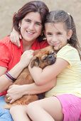 Latin girl and  her mother hugging the family dog and sitting on the grass outdoors poster