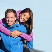 Happy hikers couple living an active lifestyle hugging laughing outdoors on trek hike nature. Healthy young people adventure fun wearing jackets. Interracial relationship, Asian woman, Caucasian man poster